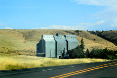 Rural Grain Elevator. An old square metal grain elevator in eastern Oregon stands on the side of the highway. Blue skies Royalty Free Stock Image