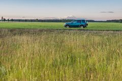 Rural grassland landscape with green off-road car Stock Images