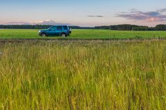 Rural grassland landscape with green off-road car Royalty Free Stock Images