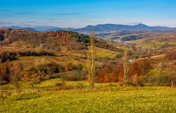 Rural grassy fields on hills in gorgeous mountains. Stunning countryside landscape in autumn Stock Image