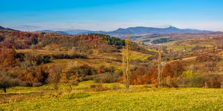 Rural grassy fields on hills in gorgeous mountains. Stunning panorama of countryside landscape in autumn Stock Photos