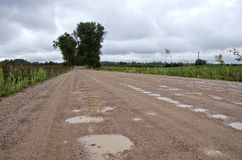 Rural gravel road with puddles after rain Stock Photography