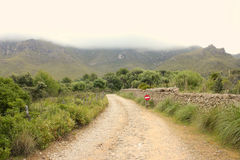 Rural gravel road to foggy mountains Royalty Free Stock Photography