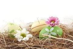 Rural horizontal view of easter eggs in the hay with flowers isolated Royalty Free Stock Image