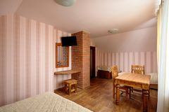 Rural Hostel Room with Brick Chimney and TV. With Wooden Furniture royalty free stock image