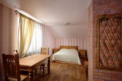 Rural Hostel Room with Hanger on Brick Chimney. With Wooden Furniture stock image