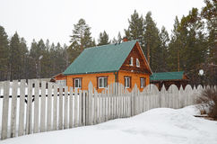 Rural house behind a fence. Spring sleet in the village. Siberia, Russia Royalty Free Stock Image