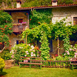 Rural house with blossom flowers in pretty cottage garden. Idyllic stone rural house with blossom flowers in summer pretty cottage garden. Square image Stock Photos