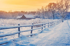 Rural house with a fence in winter. Village after snowfall stock photography