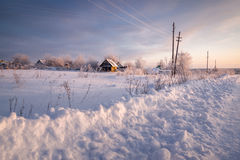 Rural house with a fence in winter. Village after snowfall on road Stock Photos