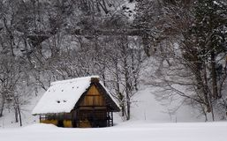 Rural House in Japan. Winter scene in Japan.  There is a wooden house called a Gasho.  There are snow covered trees visible Royalty Free Stock Photos