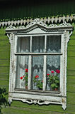 Rural house window. A window with a traditional design and flowerpots on the green wall of an old rural house royalty free stock image