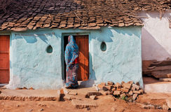 Rural house and woman in traditional sari opens the door of family home in India Stock Photography