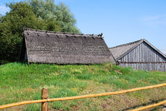 Rural houses. Rural farm scene in Latvia, the roof of a rural wooden house on a blue sky background Stock Image