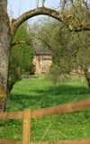 Rural idyll. A red bricked country cottage in rural Wiltshire, England viewed across a green grassed field and trees. A paddock fence to foreground Royalty Free Stock Photos