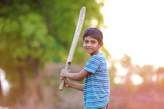 Rural Indian Child Playing Cricket. On ground Royalty Free Stock Photography