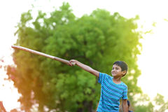 Rural Indian Child Playing Cricket. On ground Royalty Free Stock Photo