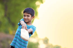 Rural Indian Child Playing Cricket. On ground Royalty Free Stock Images