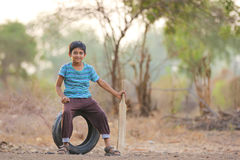 Rural Indian Child Playing Cricket. On ground Stock Images
