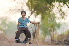 Rural Indian Child Playing Cricket. On ground Stock Photo