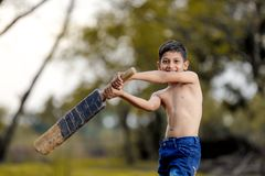 Rural Indian Child Playing Cricket.  royalty free stock images