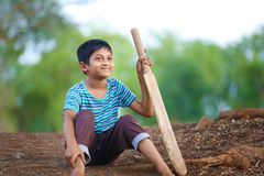 Rural Indian Child sitting on ground with bat. Playing Cricket Royalty Free Stock Photography