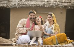 Rural Indian family using laptop on traditional bed at village royalty free stock photo