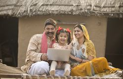 Rural Indian family using laptop on traditional bed at village royalty free stock photography