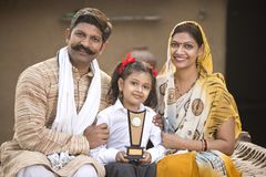 Rural Indian parents with daughter holding trophy stock images