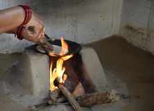 Woman preparing chapati in traditional way on a wood fired oven stock image