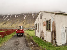 Rural Isafjordur Iceland. Red wagon and tractor and white broken down house on farmland in front of a low lying cloud and snow striped fjord in Isafjordur Stock Images