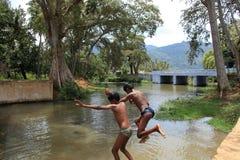 Rural kids dive in a stream Stock Photos