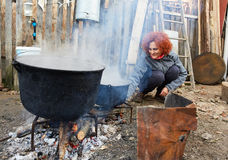 Rural lady boiling water outdoor Royalty Free Stock Images