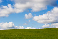 Rural landscape. Green grassland in front of the cloudy sky Royalty Free Stock Photos