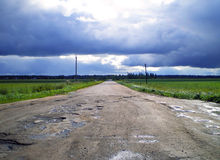 Rural landscape. Rural landscape with broken road and cloudy sky Stock Photos