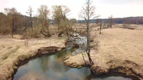 Rural landscape in april. Small River in early spring. Rural landscape in april. Small River Sula in early spring. Aerial view of brook bends in a medow. Belarus stock video footage