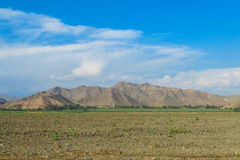 Rural landscape arable plow field. And mountains behind. Rural area, countryside Stock Image