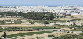 Landscape of island of Malta. Rural landscape with asphalt roads and fields on Malta. Maltese city on the background of Mediterranean sea Stock Image