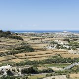 Landscape of island of Malta. Rural landscape with asphalt roads and fields on Malta. Maltese city on the background of Mediterranean sea Stock Photo