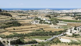 Landscape of island of Malta. Rural landscape with asphalt roads and fields on Malta. Maltese city on the background of Mediterranean sea Royalty Free Stock Photo