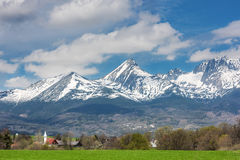 Rural landscape on a background of snow-capped mountains. Rural landscape on a background of snow-capped mountain peaks and blue sky with clouds, High Tatras Royalty Free Stock Photo
