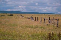 Rural landscape. Broken fence in a field Royalty Free Stock Image