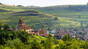 Rural landscape with Buzd Fortified Church, Romania. Landscape of rural countryside with Buzd Fortified Church and Village in Romania stock photo
