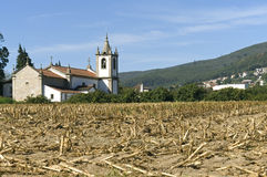 Village view with church and harvested corn field  Stock Photo
