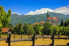 Rural landscape with church in Maddalena, Italy. Rural landscape with church and wooden fence in Maddalena, Liguria, Italy with alpine background Stock Photo