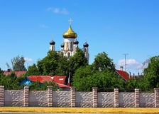 Rural landscape with church. One-storeyed wooden houses with colored roofes on rhe background of church Royalty Free Stock Images