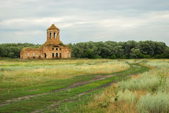 Rural landscape with church. Thrown old church on a green countryside meadow royalty free stock image