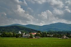 Rural landscape with a church tower and mountain slopes stock photo