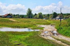 Rural landscape with dirt road, houses and power Royalty Free Stock Photo