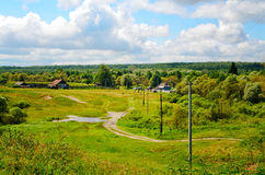 Rural landscape with dirt road, houses and power Stock Photos